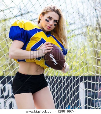 Young woman in sport clothes with ball for american football