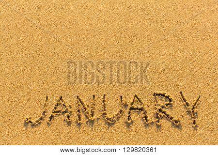 January - word inscription on the gold sand sea beach.