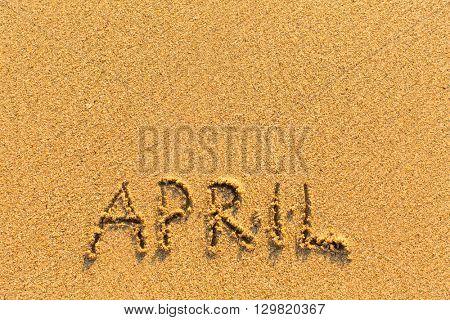 April - word inscription on the gold sand sea beach.