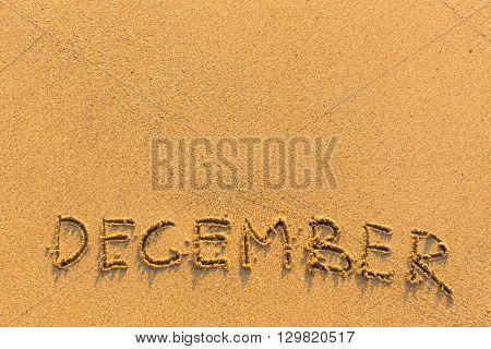 December - word inscription on the gold sand sea beach.
