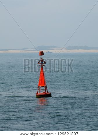 Red buoy in the misty sea marks navigable waters
