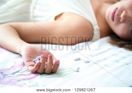 Woman's hand lying on the bed with suicide pills. Conceptual of Suicide and sadness.