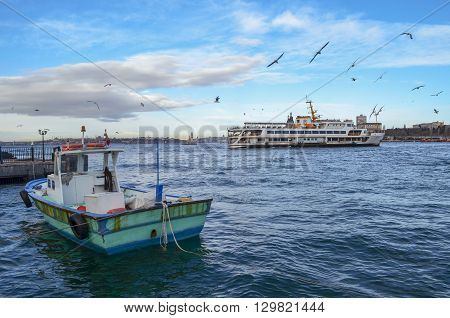 Tourist ship away and a small fishing boat seagulls a beautiful landscape.