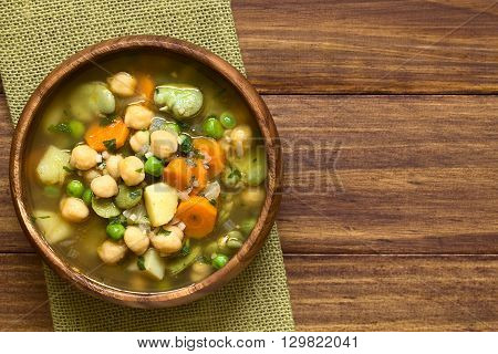 Vegetarian chickpea soup with carrot broad bean (fava bean) pea potato onion garlic and parsley served in wooden bowl photographed overhead on wood with natural light