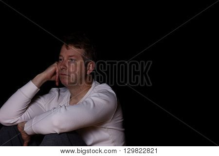 Side view of depressed mature man in thought. Dark background with copy space available.