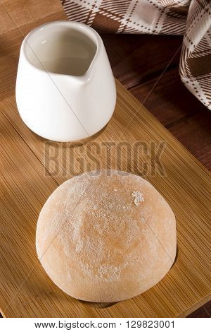 Traditional Japanese mochi on a wooden surface and a container of milk