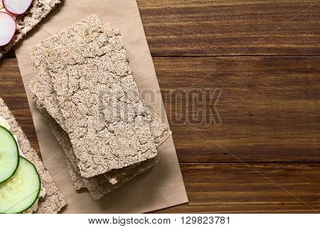 Wholemeal rye crispbread photographed overhead on dark wood with natural light (Selective Focus Focus on the upper crispbread)