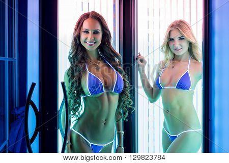Pretty smiling girls posing in modern tanning booth