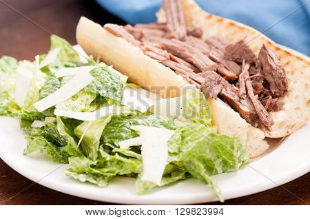 pulled brisket sandwich with a side caesar salad