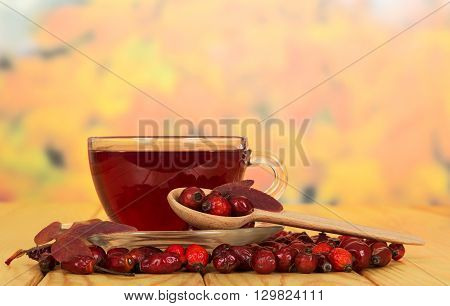 Rosehips and a cup of tea on a background of autumn leaves.