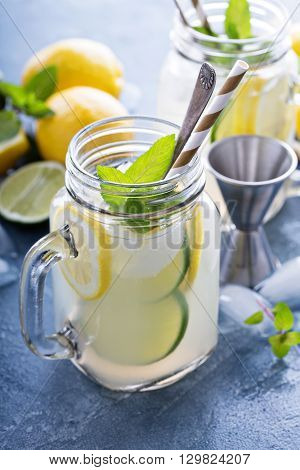 Spiked citrus lemonade with limes and lemons in mason jars