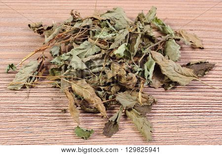Heap of healthy dried lemon balm on wooden table sedative herbs concept for healthy nutrition and herbalism