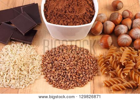 Fresh natural ingredients and products containing magnesium and dietary fiber healthy food and nutrition wholemeal pasta buckwheat brown rice hazelnut cocoa chocolate