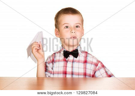 A boy sits at the table and holding a paper airplane isolated on white background.