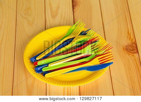 Yellow disposable plates with colored plastic knives, forks on the background of light wood.