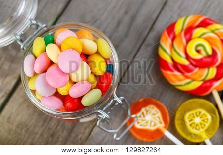Glass jar of colorful candies on a wooden table closeup with a copy space top view