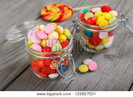 Two glass jars of colorful candy on a wooden table close up with copy space
