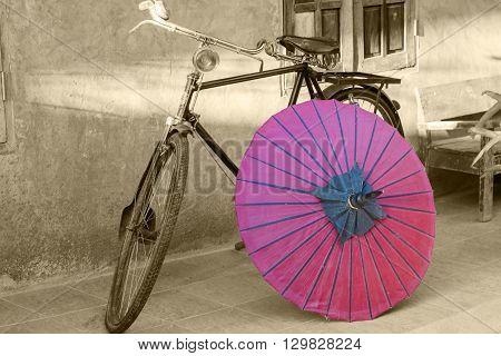 Retro bicycle with red umbrella sepia conceptual idea. Vintage retro style