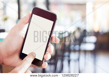 Woman using smartphone with blurred cafe background, stock photo