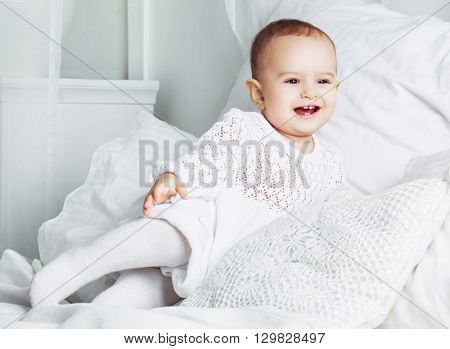 happy laughing one year old baby in bed at home