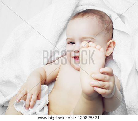 happy one year old baby with a towel in bed at home