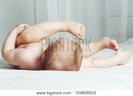 one year old baby wearing diapers in bed at home, focus on the head