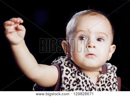 one year old baby with a hand up, stretchign for something, isolated against black background