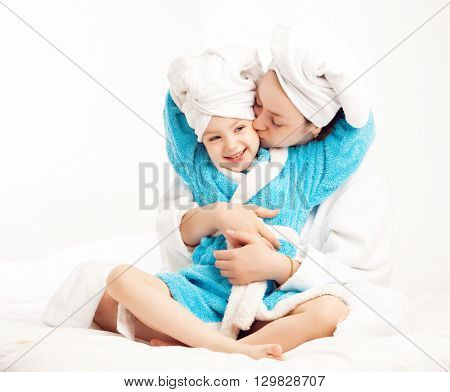 mother and daughter after shower in bed at home