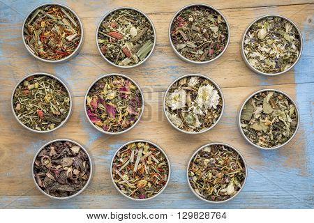 collection of eleven herbal blend Chinese tea in round metal cans, top view against painted grunge wood with a copy space