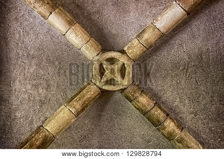 The center of a vaulted ceiling shows the stone beams centered with a circular ornament.