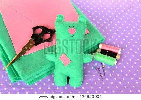 Cute green felt Teddy bear - children's toy. Scissors, threads, needles - sewing kit, needlecraft