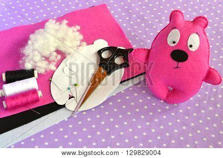 Cute felt Teddy bear - children's toy. Scissors, threads, needles, hollofayber, pins, paper patterns - sewing kit, needlecraft
