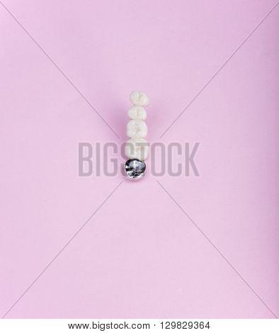 image of many dental prosthesis on pink background