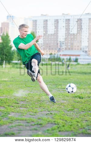 Soccer player strongly hits the ball. City park playground.