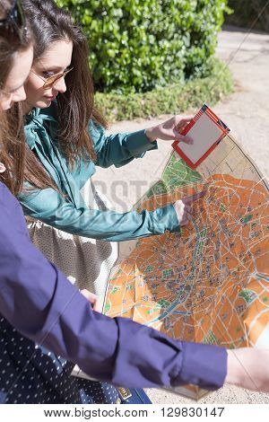 Two women holding travel map one pointing with finger