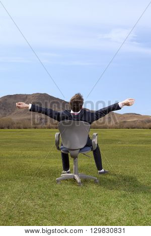 Freelancer. Businessman sitting on chair on green meadow on blue sky background
