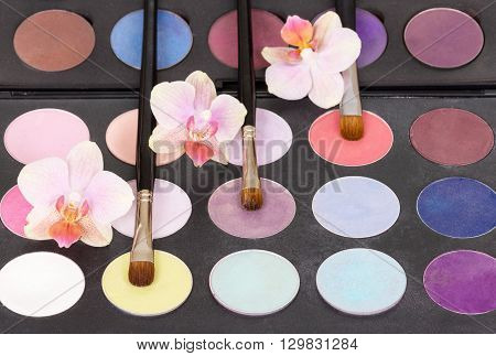 Eyeshadow palette cosmetic brushes for makeup and orchid flowers background.