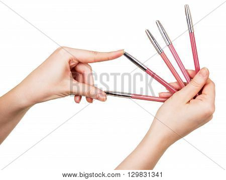 Female hand holding colorful pencils for lips isolated on white background.