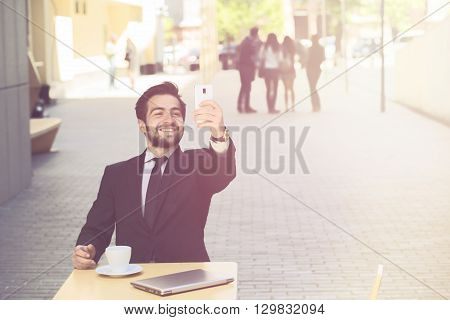 Toned image of handsome businessman making selfies on his mobile or smart phone while resting or working in restaurant or cafe in city centre.