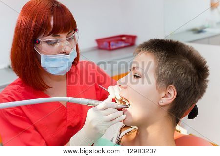 Image Of Young Lady With Dentist Over Her Checking Oral Cavity .