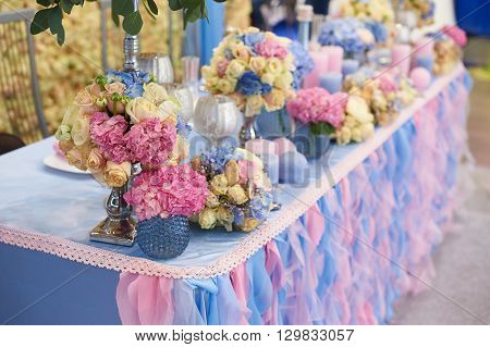 Table set for wedding reception with candles and flower bouquets.