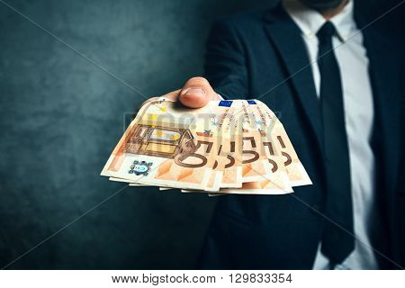 Businessman from bank offering money loan in euro banknotes selective focus.