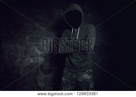Dangerous unrecognizable faceless criminal standing in front of concrete wall crime rate and gangster lifestyle concept.