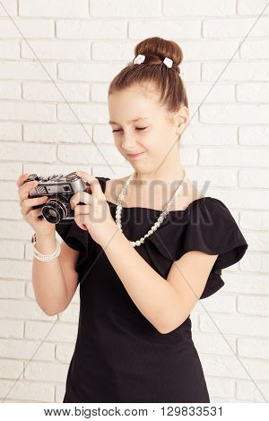 little girl holding a camera and displeased