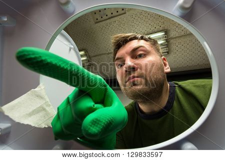 Man in rubber glove in the toilet