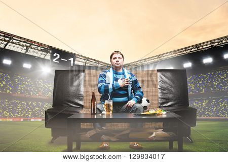 happy soccer or football fan with hand on heart on sofa at stadium