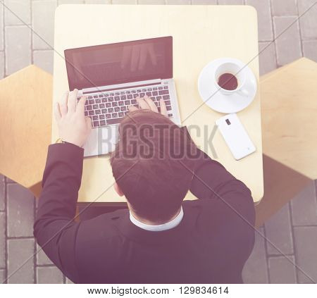 Toned image of businessman using laptop computer. Top view of handsome man searching something in Internet and looking at screen in cafe or restaurant.