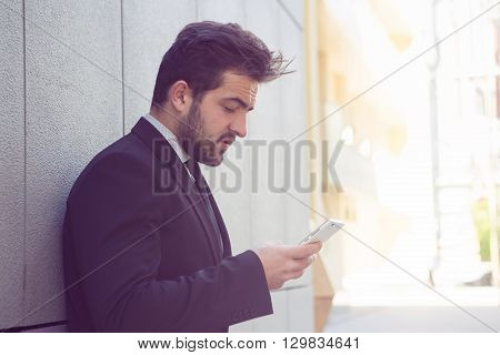 Toned picture of handsome businessman looking at mobile or smart phone's screen while stading near office building and waiting for someone.