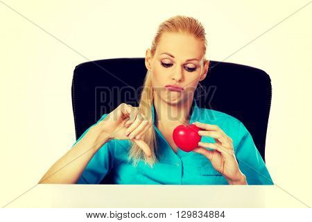 Worried female doctor or nurse sitting behind the desk holding heart model and showing thumb down