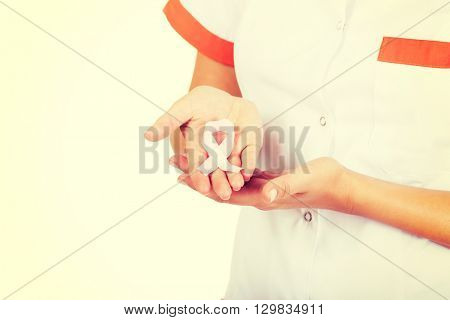 Female doctor holding pink breast cancer awareness ribbon